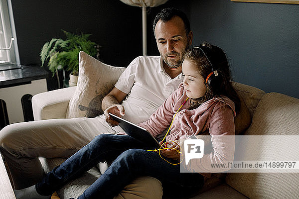 Father assisting daughter in using digital tablet on couch at home