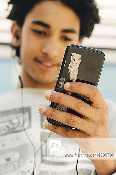 Teenage boy using mobile phone in city
