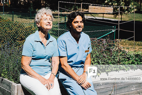 Smiling senior woman sitting with male nurse on planter at back yard