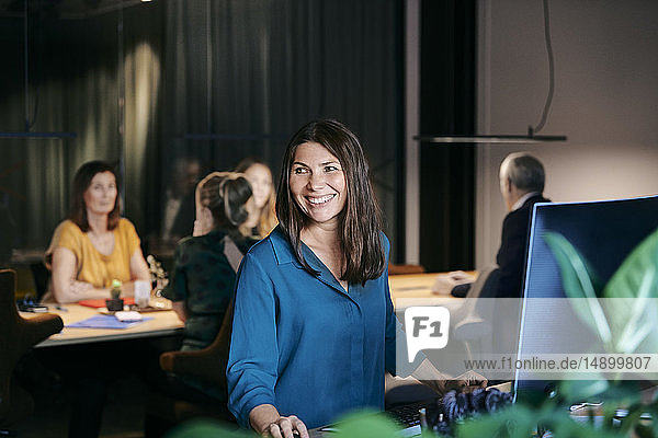 Smiling businesswoman looking away while sitting at desk against colleagues planning strategy in office