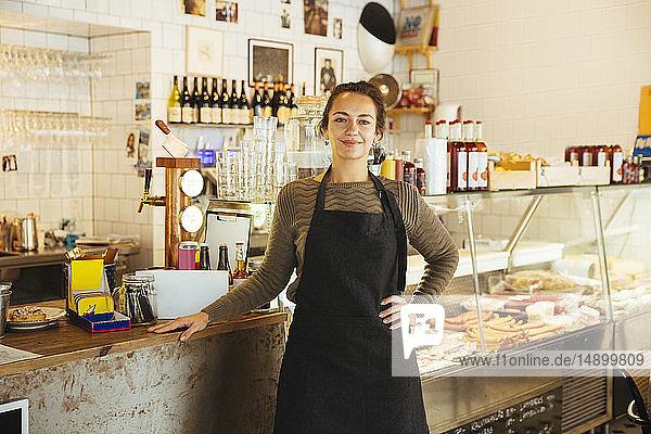 Porträt einer selbstbewussten jungen Besitzerin  die mit der Hand auf der Hüfte im Cafe steht