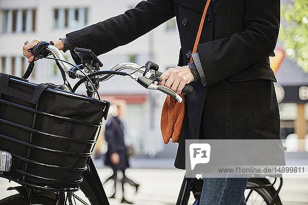 Mittelteil eines weiblichen Pendlers mit Elektrofahrrad in der Stadt