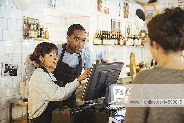 Young employee standing by female cashier using computer with customer at checkout counter in delicatessen
