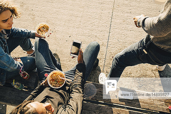 High angle view of teenage boy using smart phone while eating meal with friends on street in city