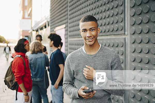 Portrait of smiling teenage boy holding mobile phone while friends standing in background on street