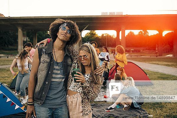 Modische Freunde mit Menschen im Hintergrund bei Musikveranstaltung