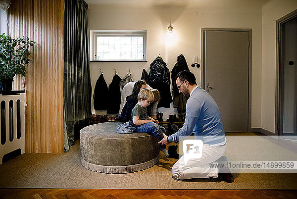 Father helping daughter in wearing shoe at home