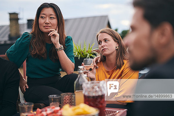 Freundinnen hören zu  während sie bei geselligem Beisammensein auf der Terrasse wegschauen