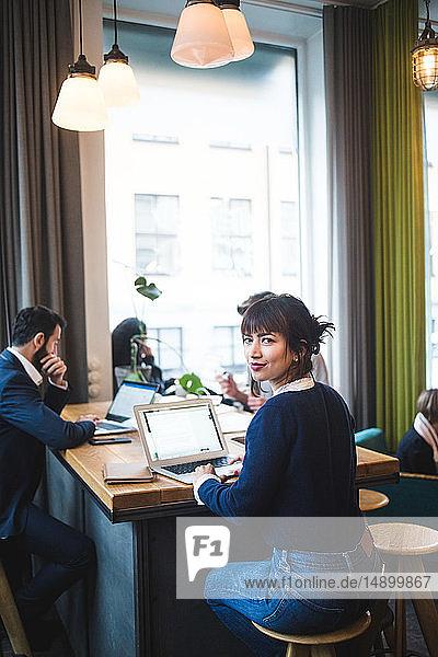 Porträt einer lächelnden berufstätigen Frau  die mit Laptop am Tisch im Büro sitzt