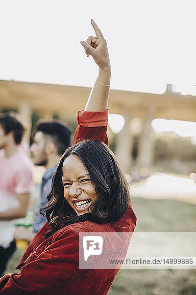 Porträt einer fröhlichen Frau  die im Sommer bei einer Musikveranstaltung tanzt