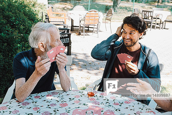 Smiling male caretaker playing cards with senior man and woman at table in back yard