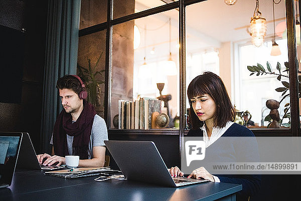 Zuversichtliche Unternehmerinnen und Unternehmer mit Laptops am Schreibtisch im Büro