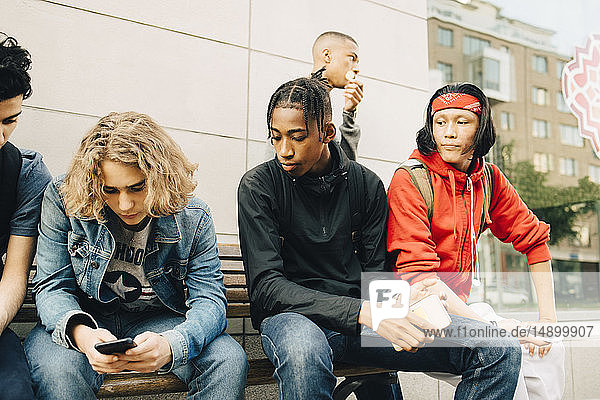 Young man using mobile phone while sitting by friends on bench at sidewalk