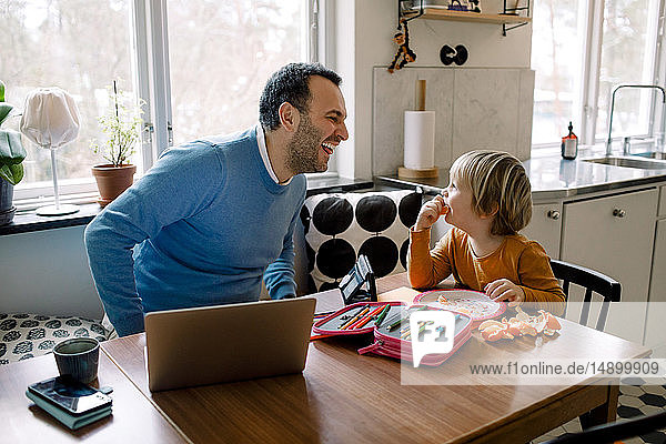 Playful father looking at daughter while using laptop at home