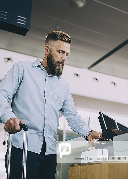 Low angle view of businessman scanning ticket on smart phone at airport check-in counter