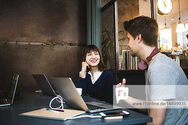 Smiling female professional looking at male colleague while planning strategy during meeting at office