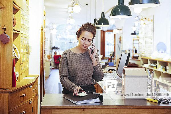 Junge Verkäuferin  die an der Kasse eines Baumarktes steht und per Handy telefoniert