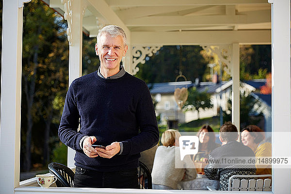 Portrait of confident smiling mature man standing on porch with friends in background