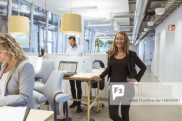 Portrait of smiling businesswoman standing at desk while colleagues working in office