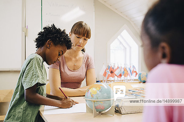 Teacher looking at boy writing on paper at table in classroom