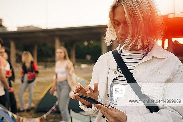 Junger Mann benutzt Mobiltelefon bei Musikveranstaltung im Sommer