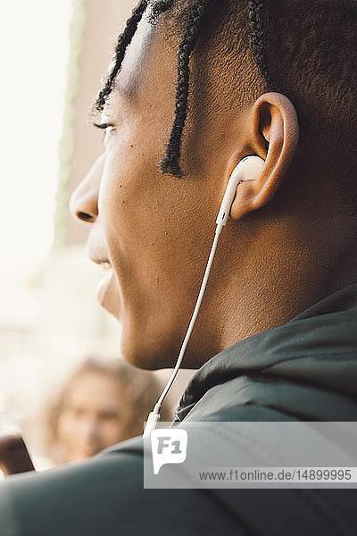 Teenage boy listening music on headphones in city