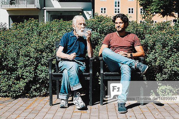 Pfeiferauchender älterer Mann im Ruhestand in voller Länge  während er mit einem männlichen Pfleger vor einem Pflegeheim sitzt