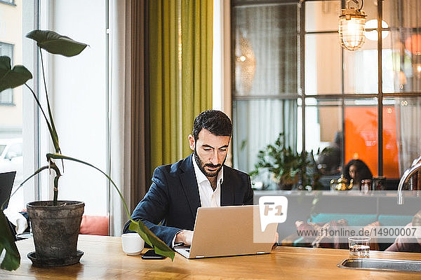 Confident male professional using laptop while sitting at table in office