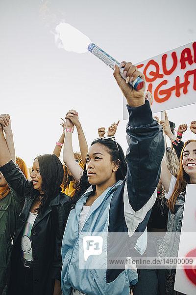 Niedrigwinkelansicht von Frauen  die während des Protests für Menschenrechte gegen den Himmel Händchen halten