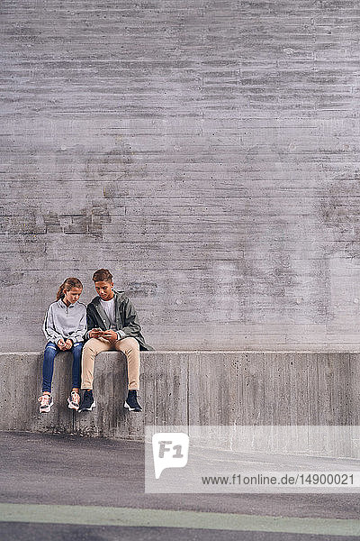 Full length of siblings using mobile phone while sitting against wall at playground