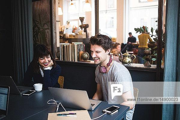 Lächelnde weibliche und männliche Kreativprofis diskutieren über Laptop am Schreibtisch im Büro