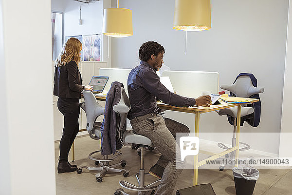 Multi-ethnic coworkers working at desk in office