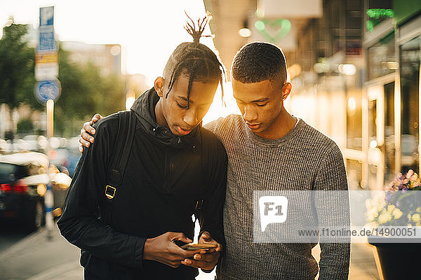 Teenage boy using mobile phone while standing by friend on street in city during sunset
