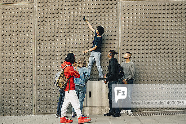 Full length of male friends taking selfie with mobile phone while standing by wall in city