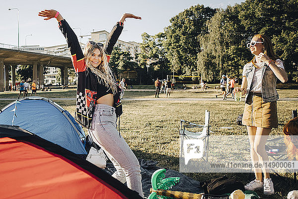 Freundinnen genießen beim Zelten während einer Musikveranstaltung