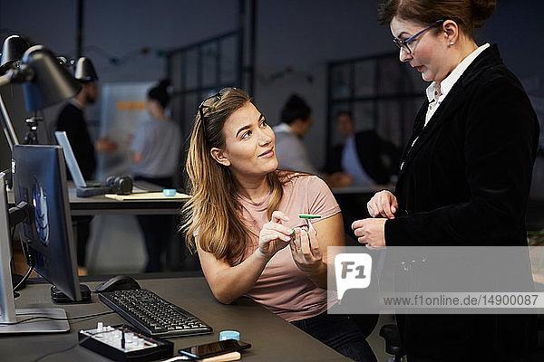 Kreative Geschäftsfrau diskutiert mit Bankmanager über Solarspielzeugauto im Kreativbüro