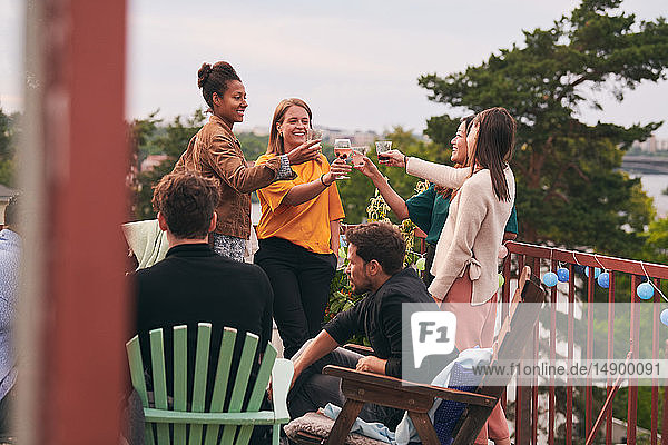 Female friends toasting drinks while men sitting on chairs during party