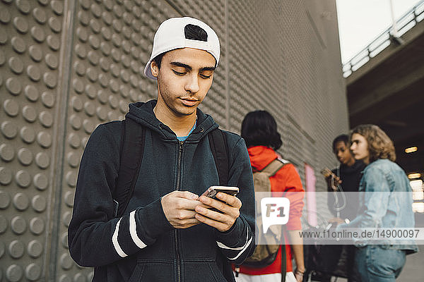 Young man using mobile phone with friends standing in background on footpath