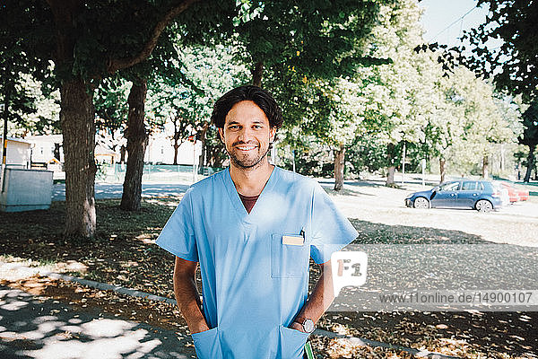 Portrait of smiling male nurse standing with hands in pockets at nursing home