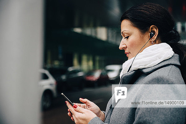 Side view of businesswoman listening music using mobile phone while standing on road in city