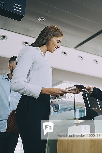 Low angle view of smiling young businesswoman checking in at airport