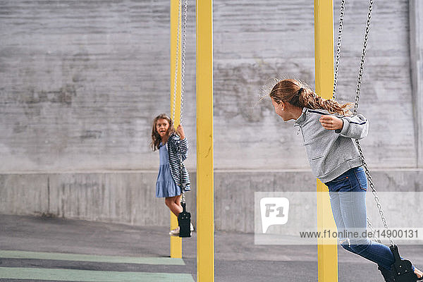 Carefree sisters swinging while standing on swings at playground