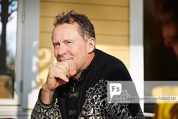 Thoughtful mature man looking away while sitting on porch