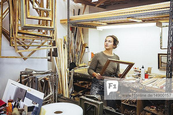 Selbstbewusste junge Handwerkerin hält den Rahmen beim Workshop