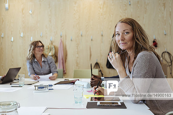 Portrait of confident businesswoman sitting at conference table with colleagues in background