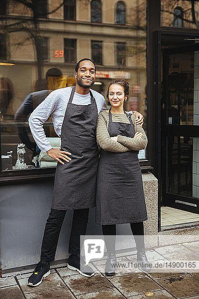 Ganzflächiges Porträt von selbstbewussten jungen Besitzern  die in der Stadt vor dem Fenster eines Feinkostladens stehen