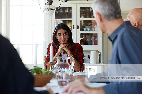 Smiling mature woman looking at male friends while sitting in dining room