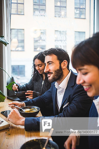 Smiling businessman eating meal with female colleagues at table in creative office