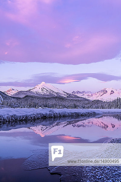 Alpenglow colours the snow-covered coastal range mountains  Mendenhall Glacier and Mendenhall towers are reflected in the open water along the edge of Auke Lake as the sun gets ready to set; Alaska  United States of America