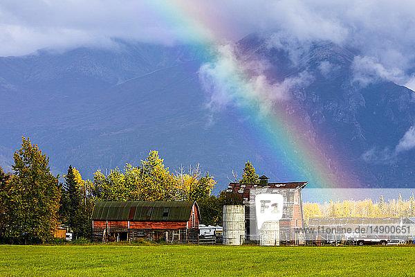 A rainbow ends over a farm  Mat-Su Valley  South-central Alaska; Palmer  Alaska  United States of America